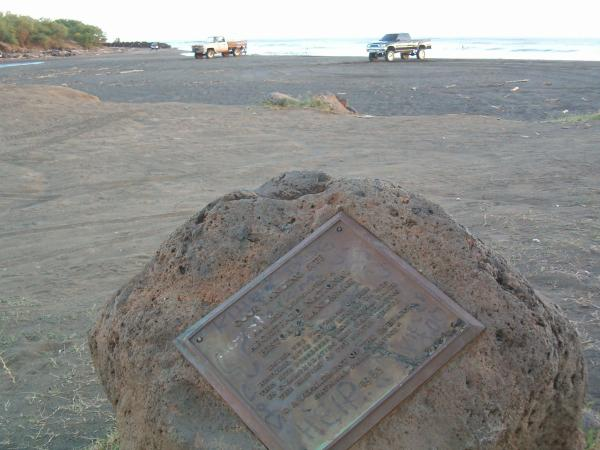 Dirty bronze plaque on a tipped over rock near two fishermans pickup trucks on the dirty black sand beach.