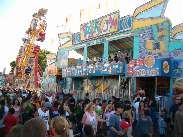 People crowd the midway rides at the fair.