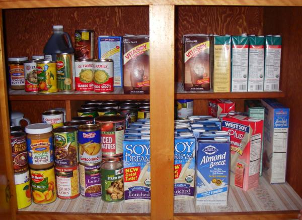 Double cupboard full of canned vegetables, fruit, soy milk cartons, and cereal boxes