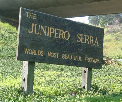 Sign saying 'Junipero Serra, the world's most beautiful freeway'