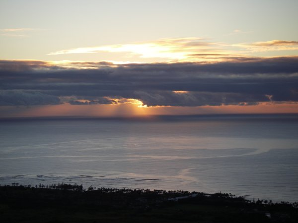 The sun hiding behind some thick low clouds on the horizon, only letting out a few rays above the silhouette of the Kapaa coast