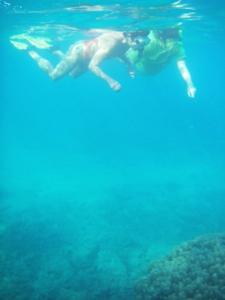 Two snorkeler floating about 10 feet (3 meters) above some coral formations in a turquoise blue ocean