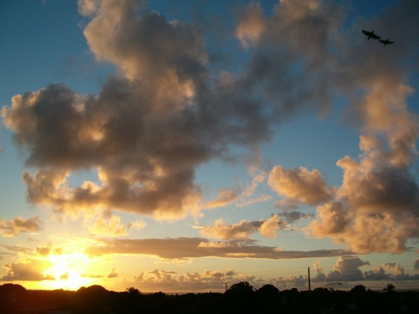 Wide-angle view of golden light from the sunrise filtering through the cumulus clouds just off the east coast at Wailua