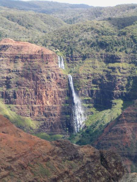 Waterfall over the red rock of Waimea Canyon, with the green carpet of the Kokee forest above.